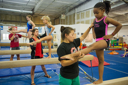 Xacha Williams (right) receives instruction on the balance beam from camp coach Stacy Scobel as Evelyn Rosselot is helped by Angelica Gillott and Phoebe Close is helped by Paula Nation during summer gymnastics camp at the Atlanta Gymnastics Center in Decatur on Tuesday, June 5, 2012. Gymnastics camp started May 29 and runs each week, Monday through Friday, until August 15.